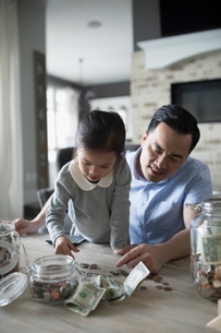 Father teaching daughter counting allowance moneyの写真素材 [FYI02317856]