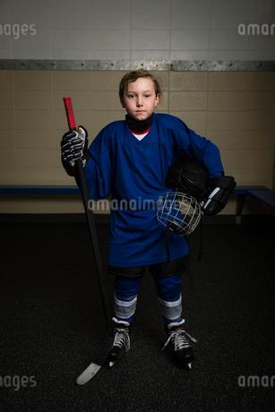 Portrait serious boy ice hockey player in uniform holding hockey stick and helmetの写真素材 [FYI02317942]