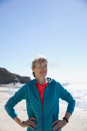 Senior female runner with hands on hips on sunny beachの写真素材 [FYI02317959]