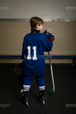 Rear view boy ice hockey player wearing number 11 uniform in locker roomの写真素材 [FYI02317963]