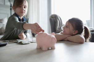 Sisters placing money in piggy bankの写真素材 [FYI02317964]