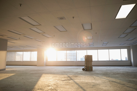 Cardboard boxes on handcart in sunny empty, unfinished highrise open plan officeの写真素材 [FYI02318017]
