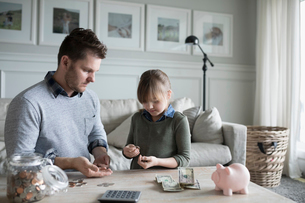 Father teaching daughter counting allowance money in living roomの写真素材 [FYI02318041]