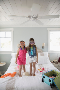 Portrait Latina sisters packing for vacation, wearing goggles on bedの写真素材 [FYI02318049]