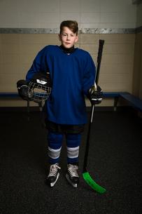 Portrait serious boy ice hockey player in uniform holding hockey stick and helmetの写真素材 [FYI02318057]