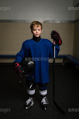 Portrait smiling boy ice hockey player in uniform holding hockey stick and helmetの写真素材 [FYI02318139]