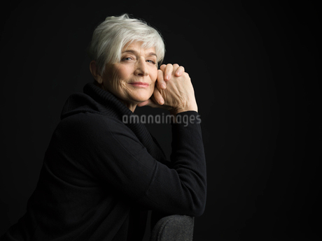 Portrait confident senior woman with short white hair against black backgroundの写真素材 [FYI02318176]