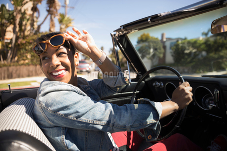 Smiling woman driving convertible, looking backの写真素材 [FYI02318233]