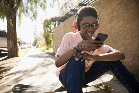 Smiling African American boy with skateboard and headphones listening to music with mp3 player on suの写真素材 [FYI02318243]
