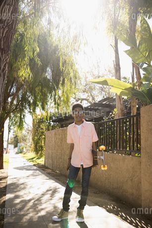 Portrait African American boy with skateboard on sunny sidewalkの写真素材 [FYI02318246]