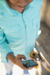 Young man with skateboard texting with smart phoneの写真素材 [FYI02318252]