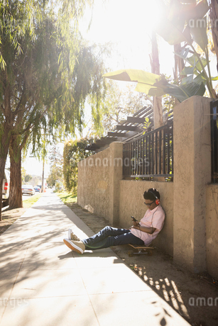 African American boy sitting on skateboard listening to music with headphones and mp3 player on sunnの写真素材 [FYI02318263]