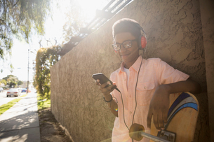 African American boy with headphones and skateboard listening to music with mp3 player on sunny sideの写真素材 [FYI02318285]