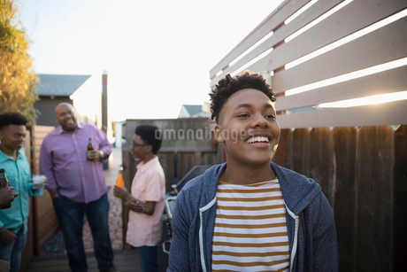 African American young man laughing with family on summer deckの写真素材 [FYI02318298]