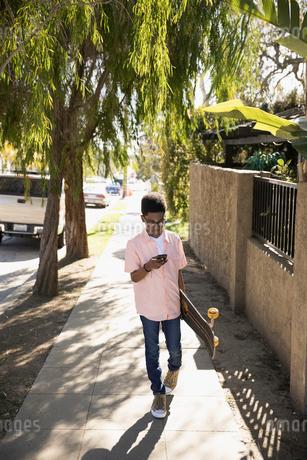 African American boy with skateboard texting and walking on sunny sidewalkの写真素材 [FYI02318329]