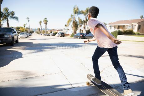 African American boy skateboarding on sunny California streetの写真素材 [FYI02318334]