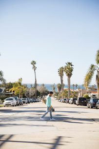 Young man with skateboard crossing sunny California streetの写真素材 [FYI02318399]