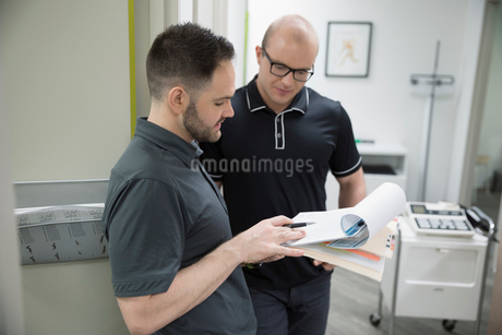 Male physiotherapists discussing medical record in clinicの写真素材 [FYI02318493]