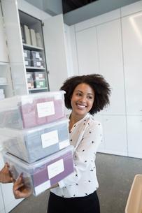 Smiling female designer carrying bins in officeの写真素材 [FYI02318506]