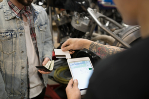 Customer paying motorcycle mechanic with credit card reader and digital tablet in auto repair shopの写真素材 [FYI02318537]