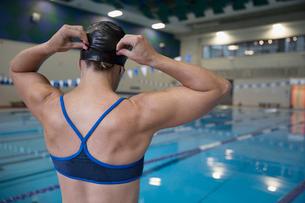 Rear view female swimmer adjusting swimming cap at swimming poolの写真素材 [FYI02318548]