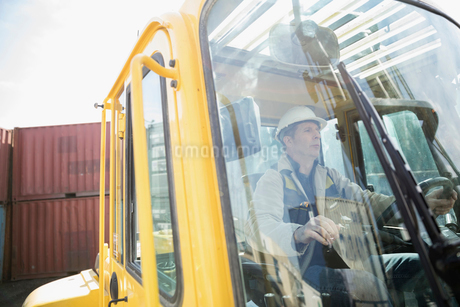 Male worker driving forklift in container yardの写真素材 [FYI02318555]