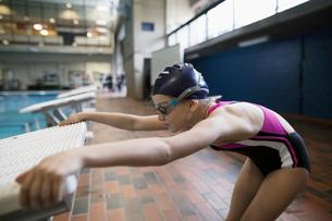 Girl swimmer stretching at starting platform at swimming poolの写真素材 [FYI02318564]