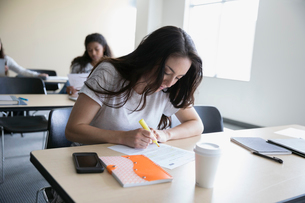Focused female college student studying in classroomの写真素材 [FYI02318587]