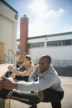Man and woman exercising, stretching legs in sunny parking lotの写真素材 [FYI02318614]