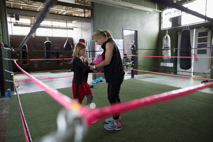 Mother boxer teaching daughter boxing in boxing ring at gymの写真素材 [FYI02318644]