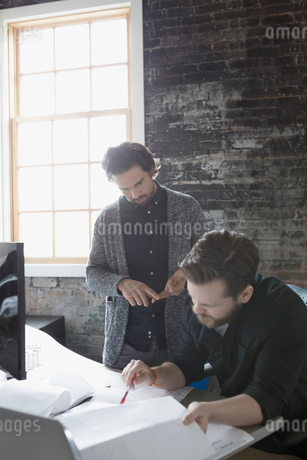 Creative businessmen reviewing paperwork in officeの写真素材 [FYI02318650]