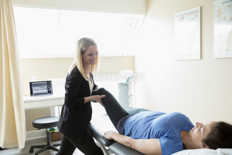 Female physiotherapist stretching woman on clinic examination roomの写真素材 [FYI02318652]
