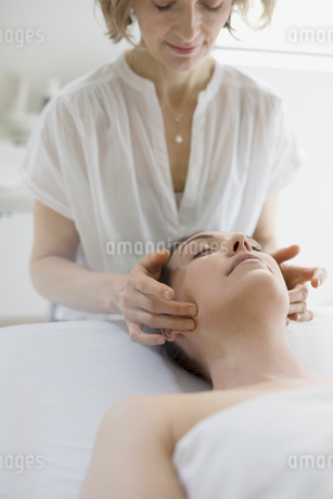 Serene woman receiving face massage on spa massage tableの写真素材 [FYI02318699]