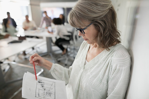 Female architect reviewing blueprints in conference room meetingの写真素材 [FYI02318708]