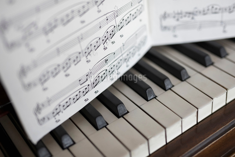 Close up sheet music over piano keysの写真素材 [FYI02318739]