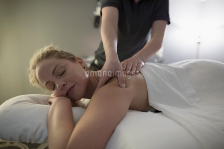 Serene woman receiving massage on spa massage tableの写真素材 [FYI02318766]