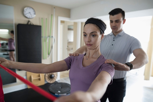 Male physiotherapist guiding female client stretching shoulders with resistance band in clinic gymの写真素材 [FYI02318833]