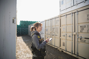 Female Caucasian worker taking notes, checking shipping containers in industrial container yardの写真素材 [FYI02318848]