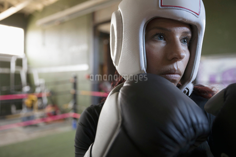 Close up serious, tough female boxer in fighting stance in boxing ringの写真素材 [FYI02318878]