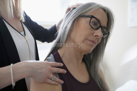 Female physiotherapist stretching neck of client in clinic examination roomの写真素材 [FYI02318882]
