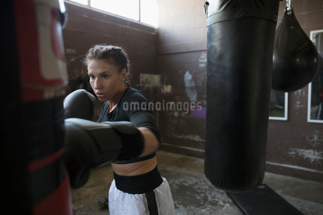 Serious, tough female boxer boxing at punching bag in gritty gymの写真素材 [FYI02318917]