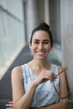 Portrait smiling businesswoman holding eyeglassesの写真素材 [FYI02318921]