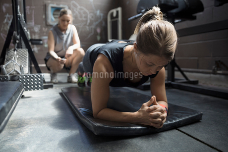 Personal trainer timing female client doing plank exercise in gritty gymの写真素材 [FYI02318932]