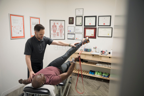 Male physiotherapist helping client stretching with resistance band in officeの写真素材 [FYI02318959]