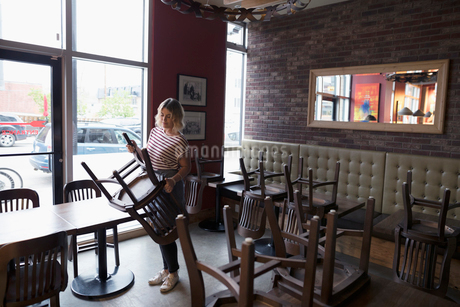 Waitress turning chairs onto tables, closing at dinerの写真素材 [FYI02318975]