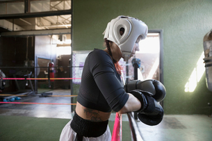 Strong, tough female boxer in protective headwear and boxing gloves, resting at rope in boxing ringの写真素材 [FYI02318981]