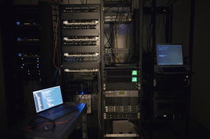 Laptop and server panels in dark server roomの写真素材 [FYI02319011]