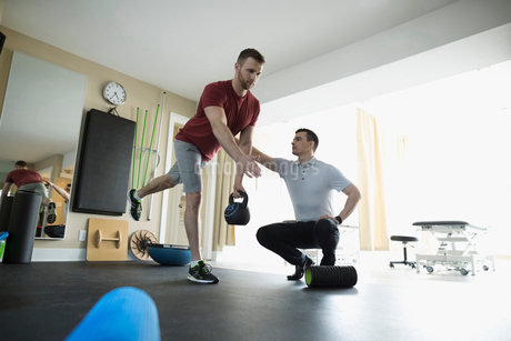 Male physiotherapist guiding client balancing with kettle bell in clinic gymの写真素材 [FYI02319028]