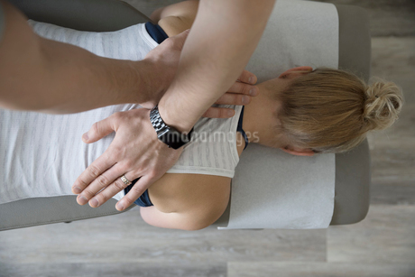Male physiotherapist massaging back of woman on clinic examination tableの写真素材 [FYI02319030]