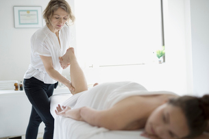 Masseuse massaging leg of woman on spa massage tableの写真素材 [FYI02319042]